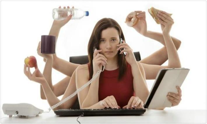 Mujer joven sentada delante de un portátil con cara de agobio y con 10 brazos. Cada brazo está realizando una tarea diferente: uno escribe en el ordenador, otro mantiene una tablet, otro sostiene teléfono fijo, otro el móvil, otro un sandwich. Representa lo absurdo de intentar realizar muchas tareas a la vez.