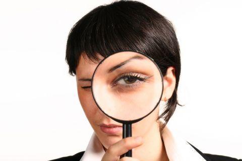 Una mujer joven con cabello oscuro corto sujetando una lupa y mirando a través de ella.